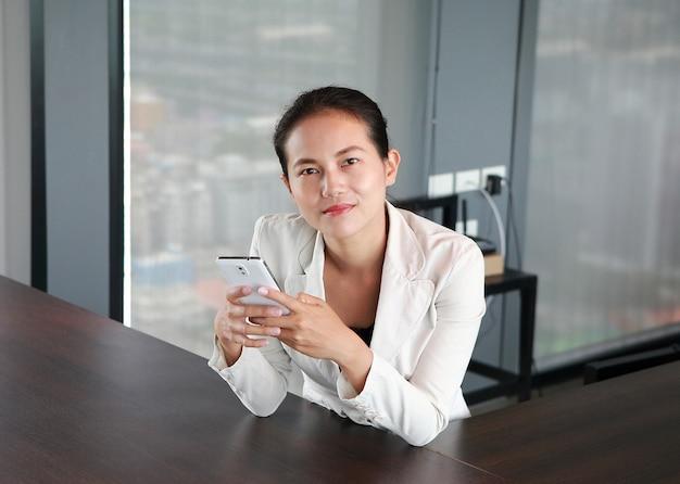 Close-up jovem empresário sentado na cadeira no local de trabalho no escritório usando o smartphone Foto Premium