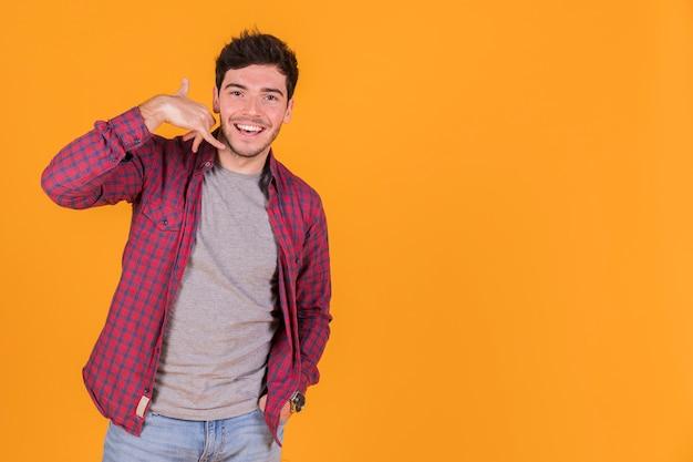 Close-up, jovem, homem, chamada, gesto, contra, laranja, fundo Foto gratuita