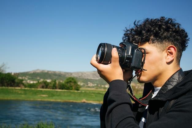 Close-up, jovem, homem, levando, fotos, dslr, câmera Foto gratuita