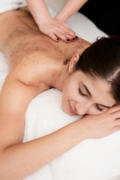 Close-up jovem morena recebendo uma massagem Foto gratuita