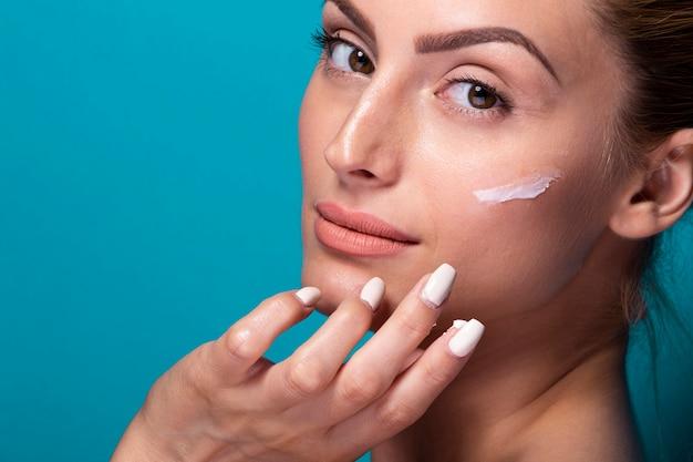 Close-up jovem mulher hidratando o rosto Foto gratuita