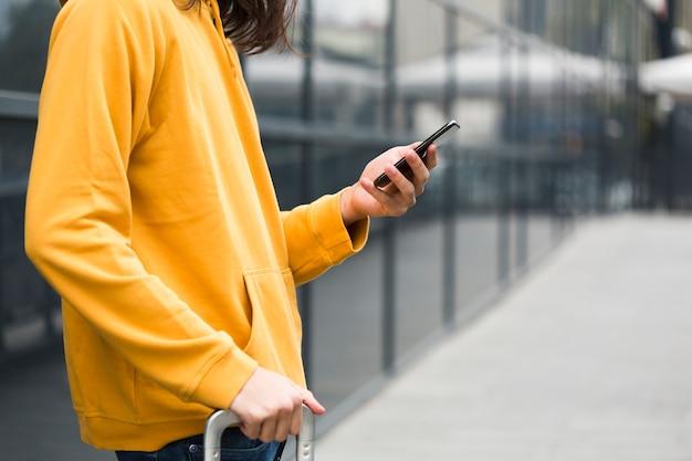 Close-up jovem viajante verificando seu telefone Foto gratuita
