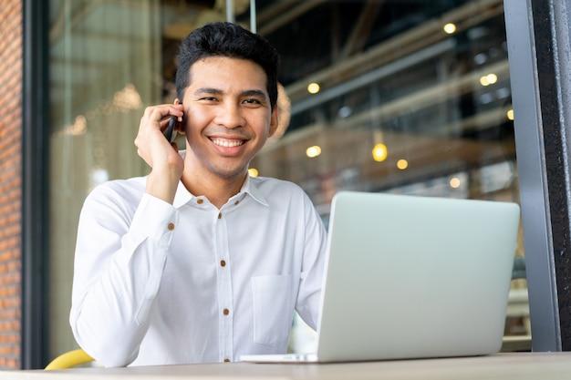 Close-up, malaio, homem negócios, falando, negócio, com, sócio, e, usando computador portátil, em, exterior, escritório Foto Premium
