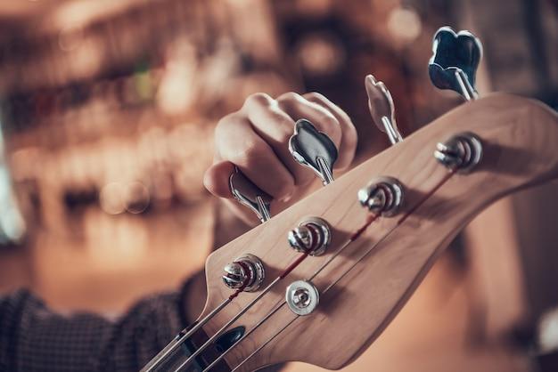 Close-up mão de homem torce pinos na guitarra fretboard Foto Premium