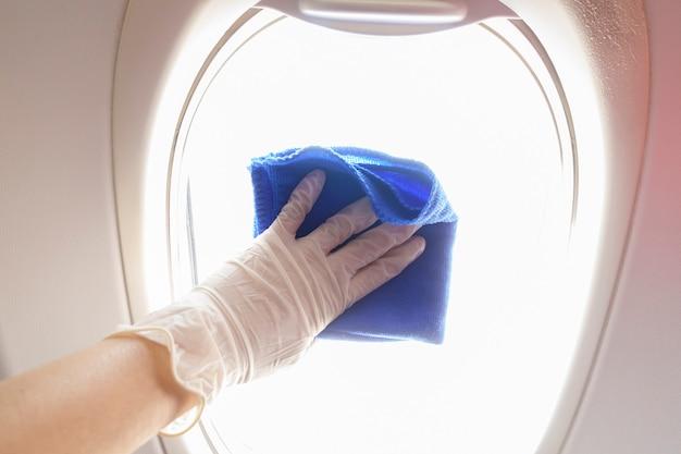 Close-up mão está usando luvas de limpeza de aeronaves para pandemia de prevenção covid-19 Foto Premium