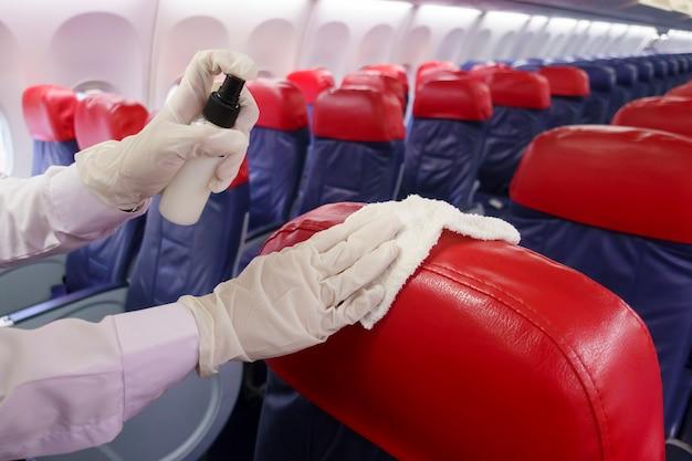 Close-up mão está usando luvas de limpeza de assento de avião para pandemia de prevenção covid-19 Foto Premium