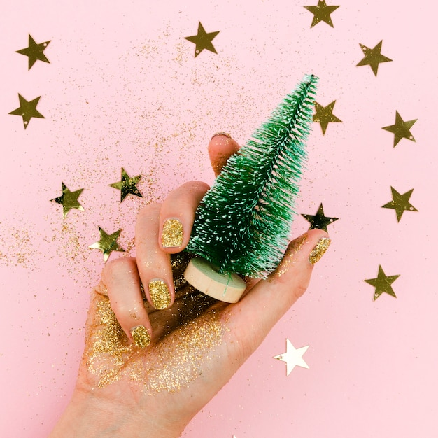 Close-up mão segurando a árvore de natal Foto gratuita