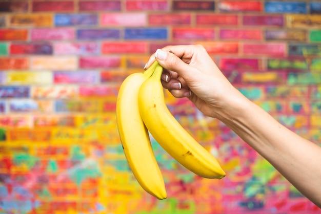 Close-up mão segurando bananas Foto gratuita