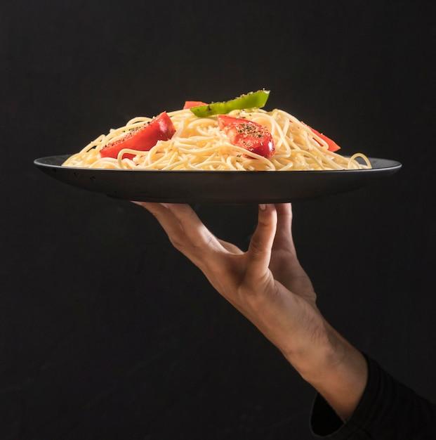 Close-up mão segurando o prato com macarrão Foto gratuita