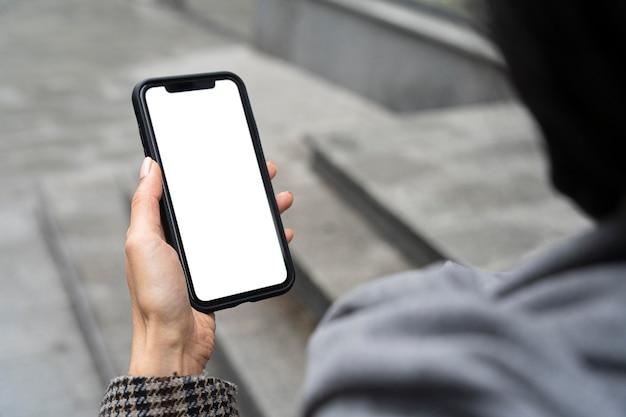 Close-up mão segurando o telefone Foto gratuita
