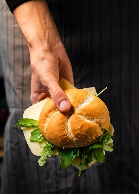 Close-up mão segurando pão fresco Foto gratuita