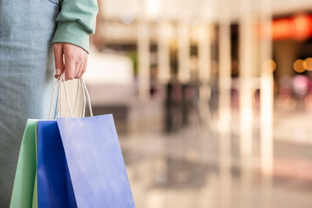Close-up mão segurando sacolas de compras Foto Premium
