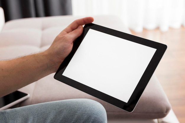 Close-up mão segurando tablet Foto gratuita