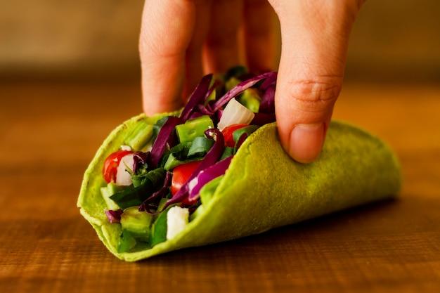 Close-up mão segurando taco vegetariano Foto gratuita