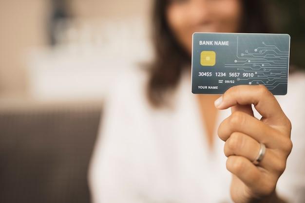 Close-up mão segurando um cartão de crédito simulado Foto Premium