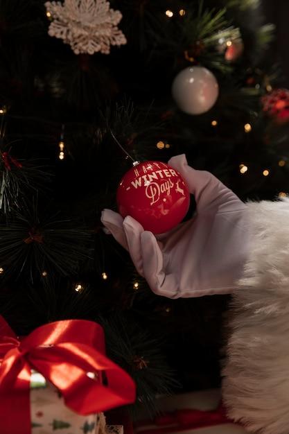 Close-up mão segurando uma bola de natal Foto gratuita