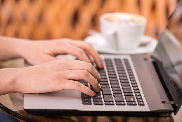 Close-up mãos de mulher jovem está usando o laptop. Foto Premium