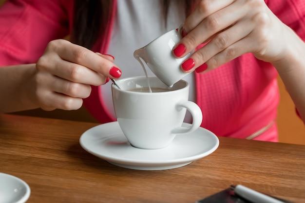 Close-up, mãos de uma jovem garota, derrama creme ou leite no café em um café na mesa de madeira. Foto Premium