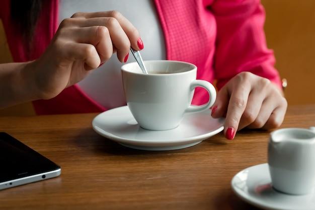 Close-up, mãos de uma jovem garota, mexe açúcar em uma xícara de café, senta-se em um café atrás de uma madeira stolikos Foto Premium