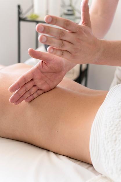 Close-up mãos massageando as costas Foto gratuita