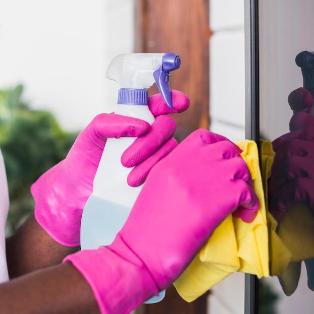 Close-up mãos segurando material de limpeza Foto gratuita