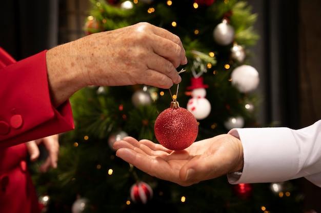 Close-up mãos segurando uma bola de natal Foto gratuita