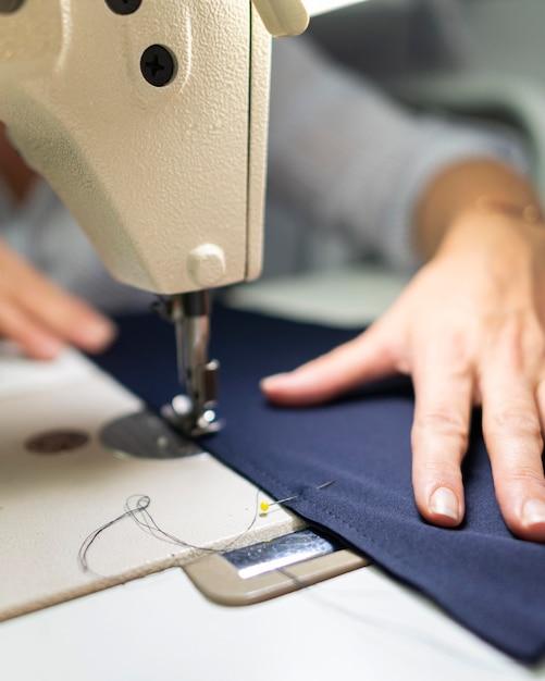 Close-up mãos usando máquina de costura Foto gratuita