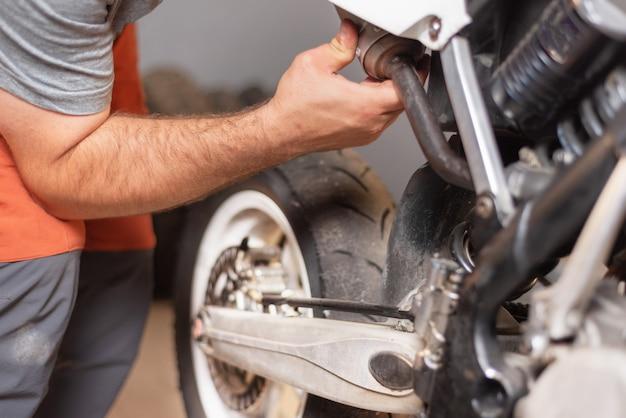 Close-up mecânico reparação de moto na garagem de reparação. Foto Premium