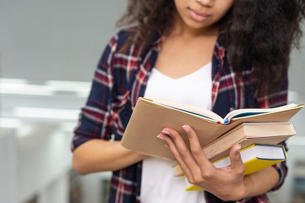 Close-up, menina, carregar, pilha livros, durante a leitura Foto gratuita