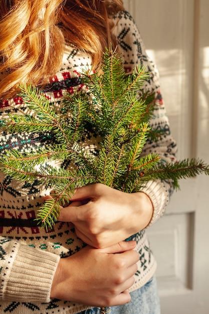 Close-up, menina, segurando, abeto, árvore galhos Foto gratuita