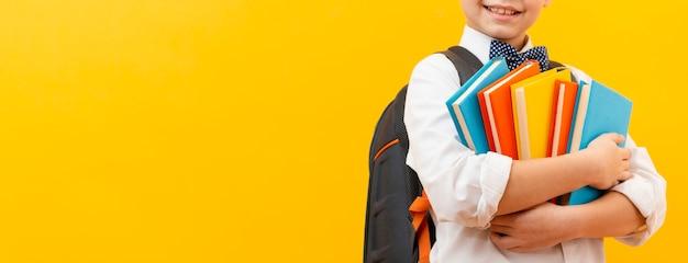 Close-up, menino, carregar, pilha livros Foto gratuita