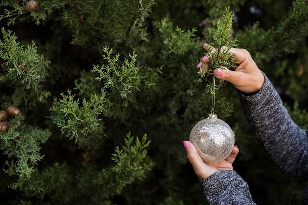 Close-up mulher a decorar a árvore de natal com globo Foto gratuita