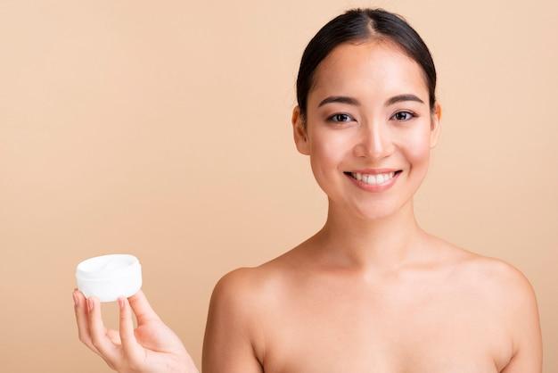 Close-up, mulher asiática, segurando, jarro creme Foto gratuita