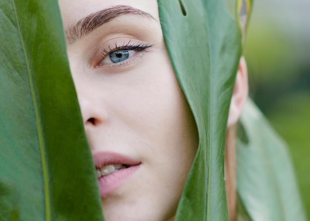 Close-up mulher assistindo através de folhas Foto gratuita