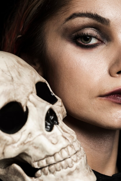 Close-up mulher com crânio humano Foto gratuita