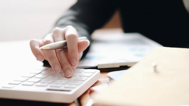 Close-up mulher de negócios usando a calculadora e laptop para fazer contas de matemática na mesa de madeira Foto Premium
