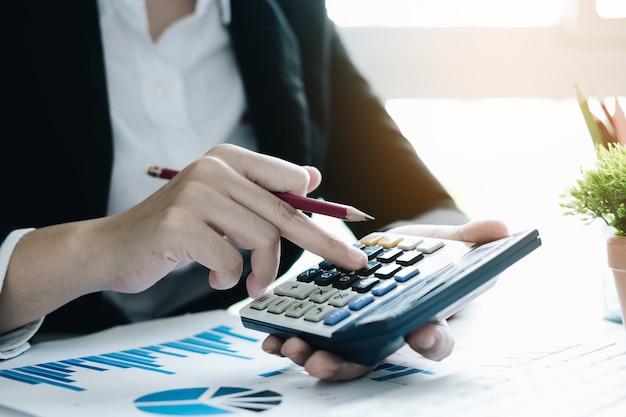 Close-up mulher de negócios usando a calculadora para fazer finanças matemática na mesa de madeira no escritório e negócios, trabalho, impostos, contabilidade, estatística e conceito de pesquisa analítica Foto Premium