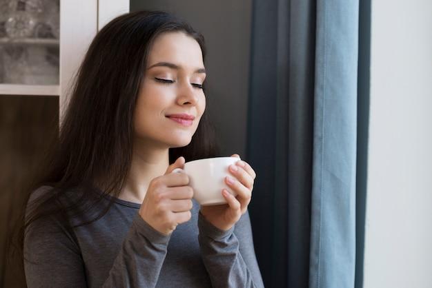 Close-up mulher jovem e bonita desfrutando de uma xícara de café Foto gratuita