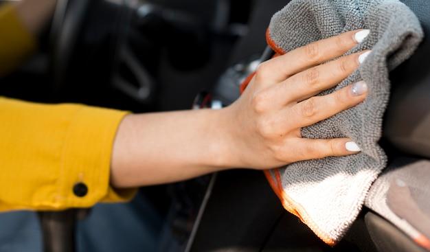 Close-up mulher limpando o carro Foto gratuita