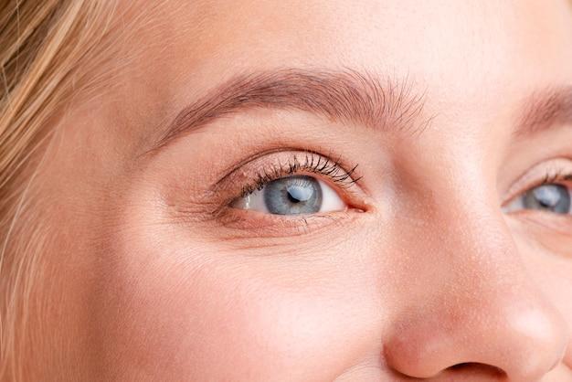 Close-up mulher loira com lindos olhos azuis Foto gratuita