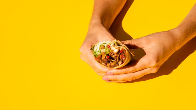 Close-up mulher segurando saboroso burrito Foto gratuita