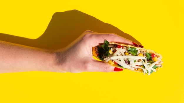 Close-up mulher segurando taco com fundo amarelo Foto gratuita