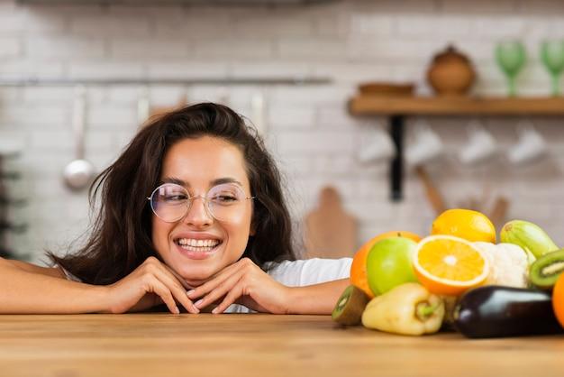 Close-up mulher sorridente, olhando para as frutas Foto gratuita