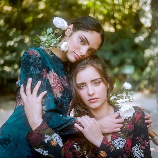Close-up, mulheres, em, vestidos florais, segurando, um ao outro Foto gratuita