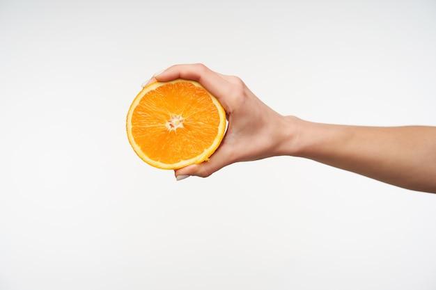 Close-up na metade da laranja fresca sendo segurada pela mão de uma jovem Foto gratuita