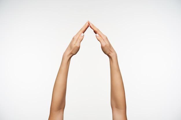 Close-up nas mãos de uma mulher sendo levantadas enquanto imita o sinal de casa Foto gratuita