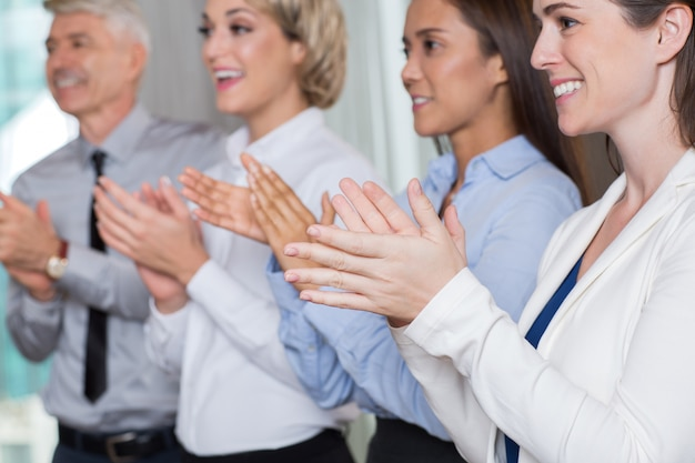 Close up of four executivos de sorriso de aplaudir Foto gratuita