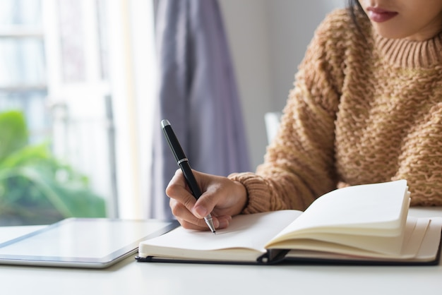 Close-up, pensativo, mulher, escrevendo, idéias, em, diário Foto gratuita