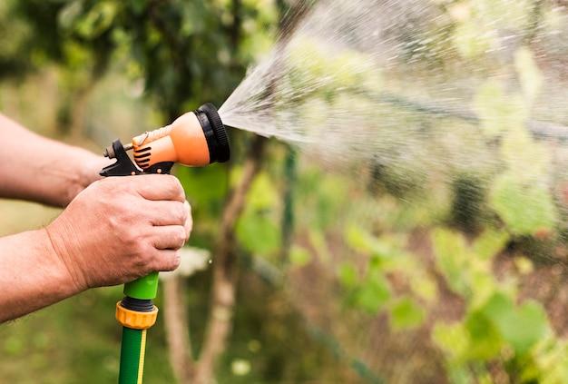 Close-up, pessoa, com, mangueira água Foto gratuita
