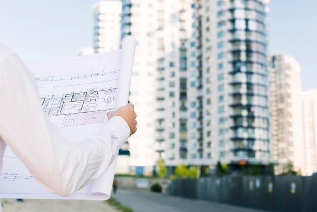 Close-up pessoa segurando planos de construção Foto gratuita
